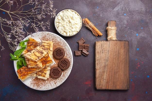 Vista dall'alto deliziosi pasticcini dolci con biscotti al cioccolato sulla scrivania scura