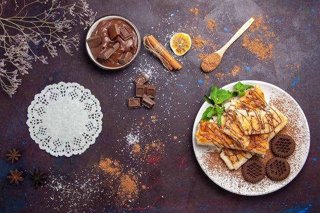 Vista dall'alto deliziosi pasticcini dolci con biscotti al cioccolato su un pavimento scuro tè torta zucchero biscotto dolce dessert