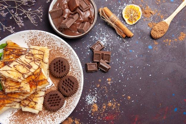 Vista dall'alto deliziosi pasticcini dolci con biscotti al cioccolato sullo spazio buio