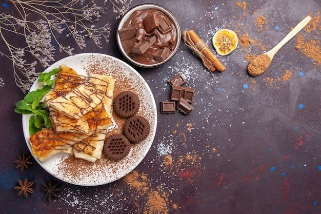 어두운 바닥 케이크 설탕 비스킷 차 달콤한 디저트에 초콜릿 쿠키와 상위 뷰 맛있는 달콤한 파이