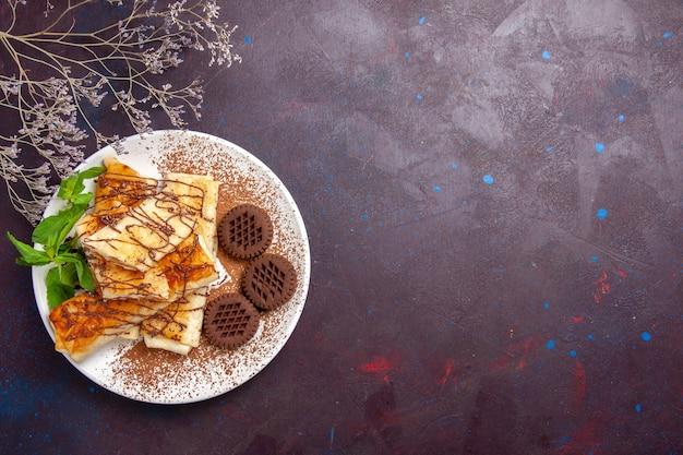 暗い空間にチョコレートクッキーとトップビューのおいしい甘いペストリー