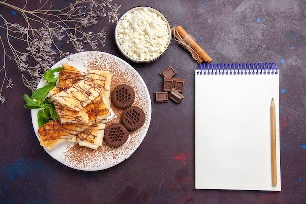 Вид сверху вкусной сладкой выпечки с шоколадным печеньем на темном пространстве