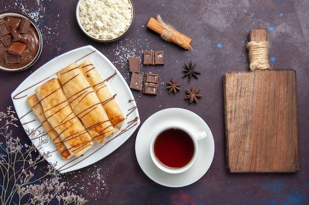 Vista dall'alto deliziosi pasticcini dolci con cioccolato e tazza di tè sulla scrivania scura