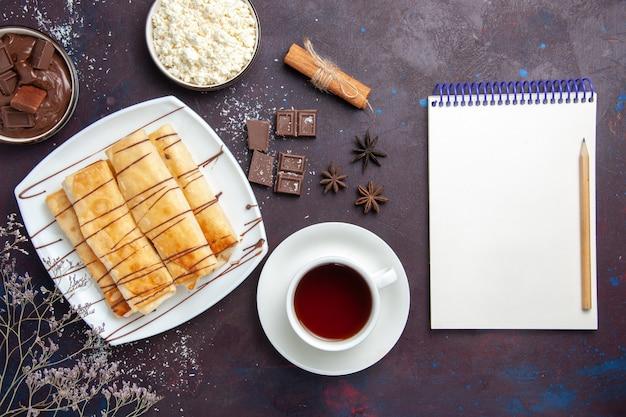 Vista dall'alto deliziosi pasticcini dolci con cioccolato e tazza di tè sul pavimento scuro cuocere dolce zucchero torta biscotto dolce