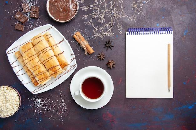 Vista dall'alto deliziosi pasticcini dolci con cioccolato e tazza di tè nello spazio buio