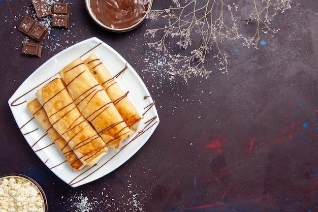 Vista dall'alto deliziosi pasticcini dolci con cioccolato su spazio viola scuro