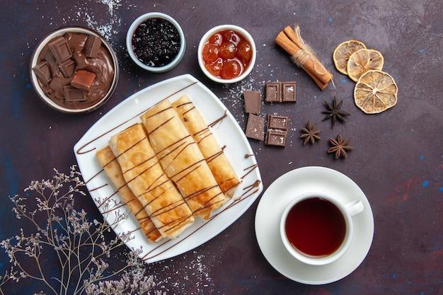 暗い空間でチョコレートジャムとお茶のトップビューおいしい甘いペストリー