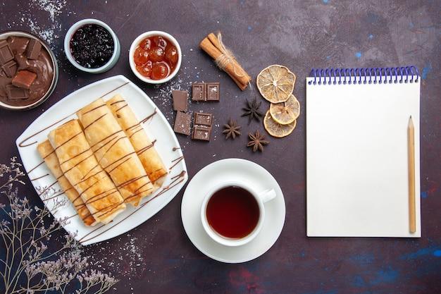 Вид сверху вкусной сладкой выпечки с шоколадным джемом и чашкой чая на темном столе