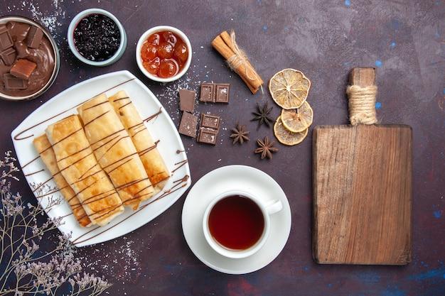 Vista dall'alto deliziosi pasticcini dolci con marmellata di cioccolato e tazza di tè sul pavimento scuro cuocere dolce zucchero torta biscotto dolce