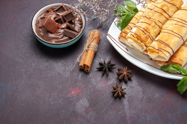 Вид сверху вкусной сладкой выпечки с шоколадом на темном пространстве