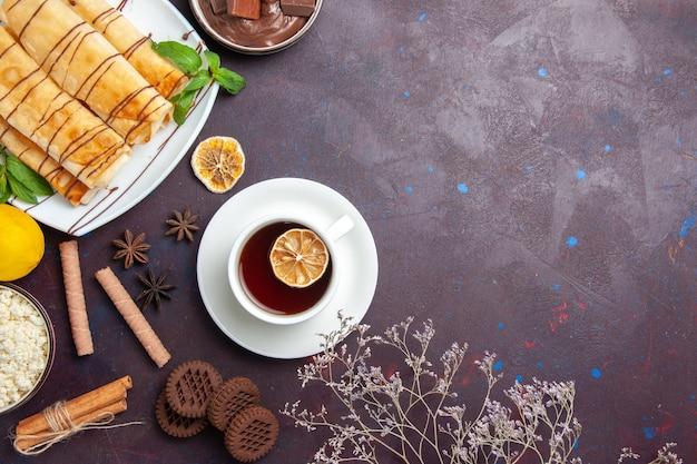 Вид сверху вкусной сладкой выпечки с печеньем и чаем на темном пространстве