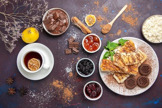 Vista dall'alto deliziosi pasticcini dolci con biscotti e tazza di tè in uno spazio buio