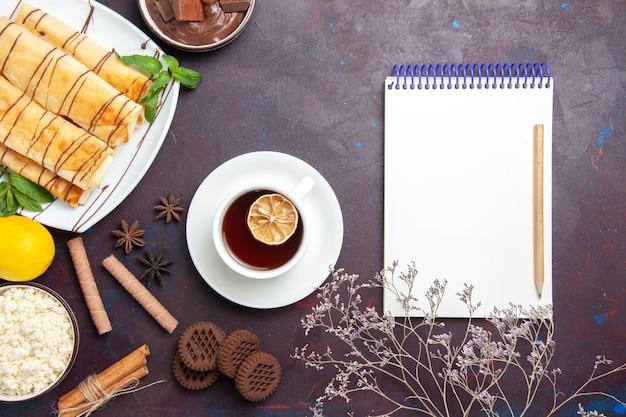Vista dall'alto deliziosi pasticcini dolci con biscotti e tè sulla scrivania scura