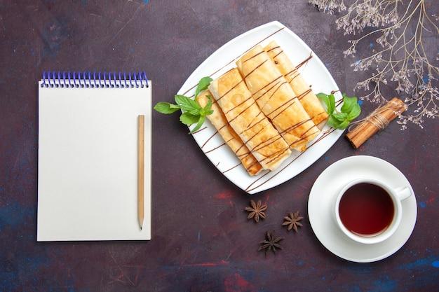 暗い空間にお茶とメモ帳を備えたトップビューのおいしい甘いペストリー