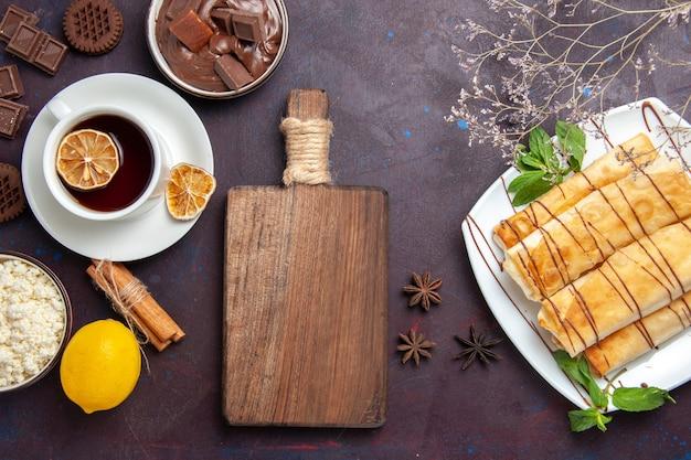 Vista dall'alto deliziosi pasticcini dolci con una tazza di tè al cioccolato e biscotti sulla scrivania scura