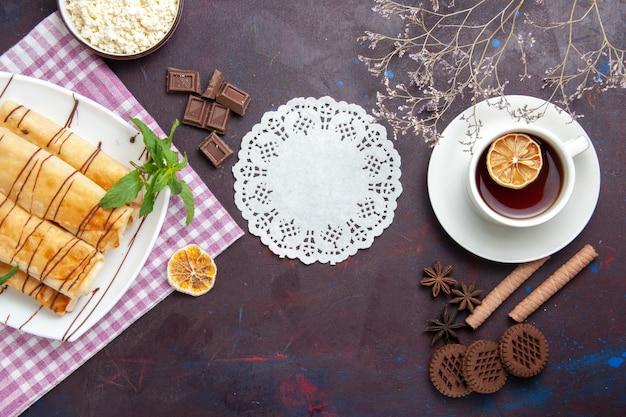 Vista dall'alto deliziosi pasticcini dolci con una tazza di tè e biscotti nello spazio buio