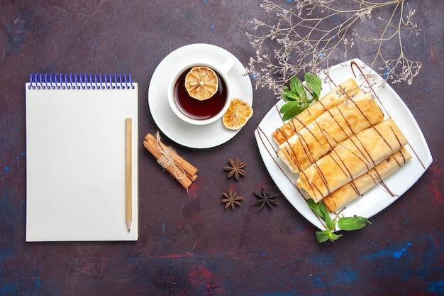 Vista dall'alto deliziosi pasticcini dolci con una tazza di tè nello spazio buio