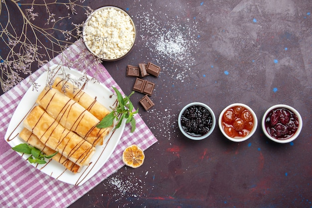 暗い空間でジャムとカッテージチーズとトップビューのおいしい甘いペストリー