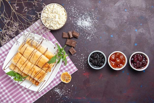 Vista dall'alto deliziosi pasticcini dolci con marmellata e ricotta su uno spazio buio