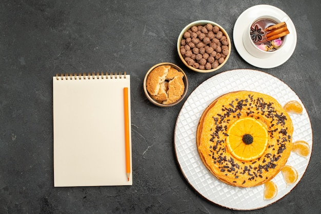 Top view delicious sweet pie with cup of tea on dark grey surface cookie pie biscuit dessert tea cake