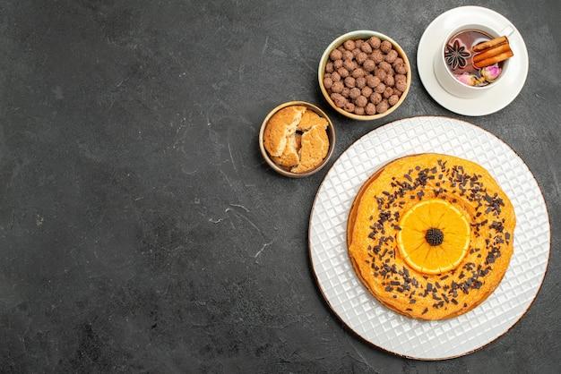 Vista dall'alto deliziosa torta dolce con una tazza di tè sulla superficie scura torta di biscotto biscotto dessert torta di tè