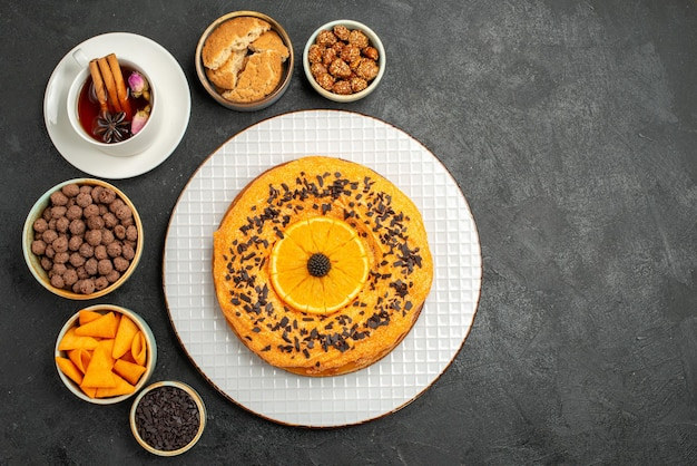 Top view delicious sweet pie with orange slices and cup of tea on dark surface cookie pie biscuit cake dessert tea
