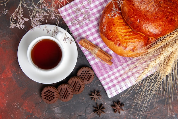 Top view delicious sweet pies with cup of tea on a dark table cake sweet pie pastry