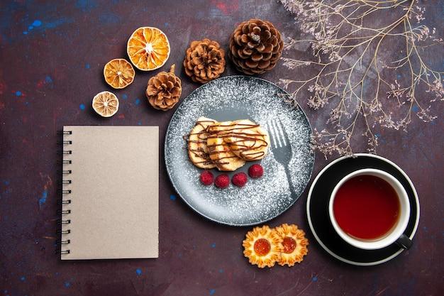 상위 뷰 맛있는 달콤한 롤 어두운 배경에 차 한잔에 대한 케이크를 슬라이스 롤 비스킷 달콤한 파이 케이크 차 디저트