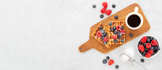 Top view delicious sweet waffles and coffee on wooden board