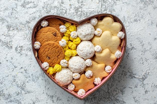 上面図白い表面のハート型の箱の中のおいしいお菓子ビスケットクッキーとキャンディーシュガーケーキパイティー甘いおいしい