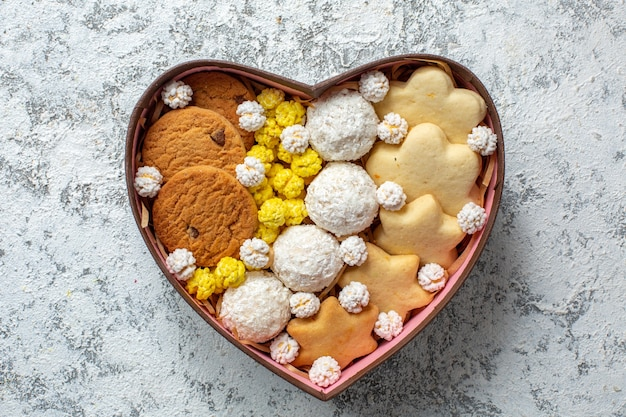Top view delicious sweets biscuits cookies and candies inside heart shaped box on a white surface sugar cake pie tea sweet yummy