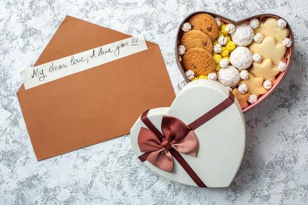 Vista dall'alto deliziosi dolci biscotti biscotti e caramelle all'interno di una scatola a forma di cuore su una superficie bianca torta di zucchero tè dolce yummy cake