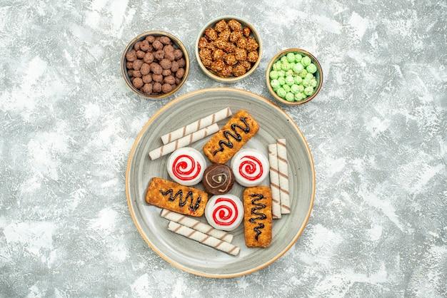 Vista dall'alto deliziosi dolci torte e biscotti su uno spazio bianco chiaro