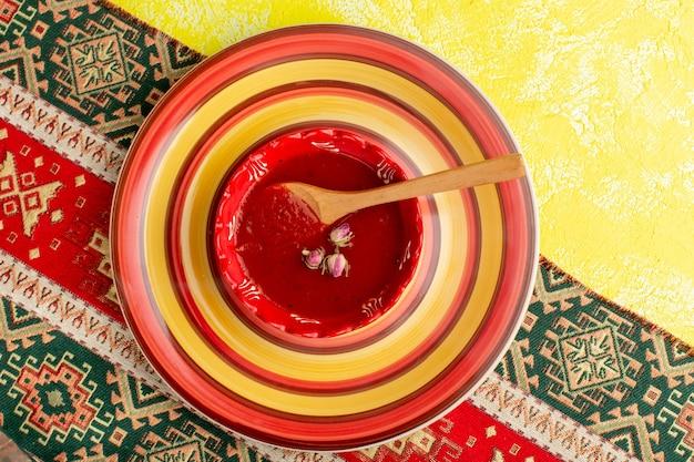 黄色いテーブルスープフードミールディナーのプレート内のおいしいトマトソースの上面図