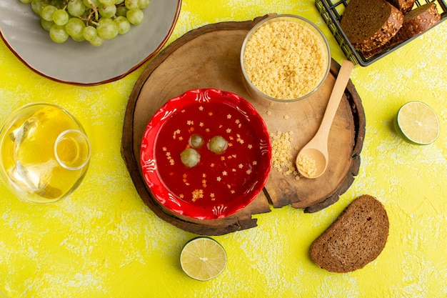 黄色いテーブルスープミール野菜料理にパンとおいしいトマトソースの上面図