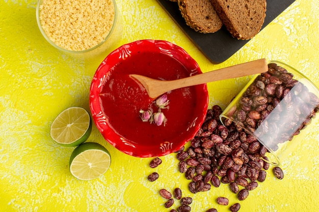Vista dall'alto deliziosa salsa di pomodoro con pagnotte di pane scuro limone e fagioli crudi sulla cena di pasto cibo zuppa gialla scrivania
