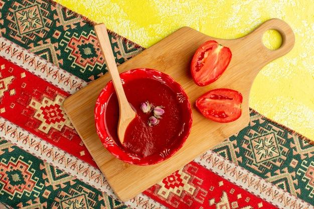 トップビュー黄色い机の上の新鮮な赤いトマトとおいしいトマトソーススープフードミールディナー
