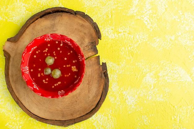 黄色い机の上の緑のブドウとおいしいトマトソースの上面図スープフードミールディナー