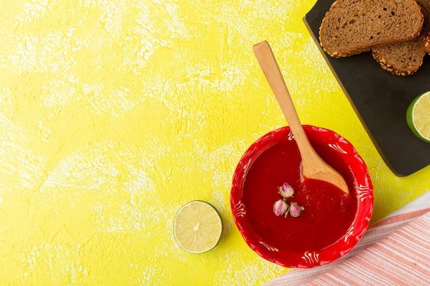 Vista dall'alto deliziosa salsa di pomodoro con limone e pagnotte di pane sul cibo vegetale pasto giallo zuppa di tabella