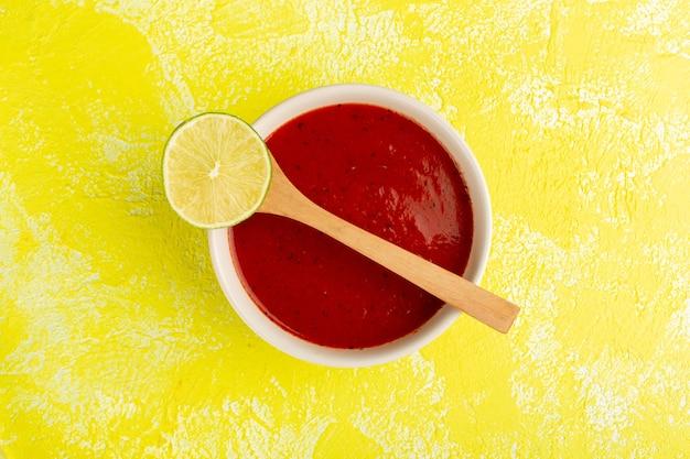トップビュー黄色のテーブルにレモンとおいしいトマトソース、スープ料理食事ディナー