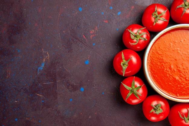 Vista dall'alto deliziosa zuppa di pomodoro circondata da pomodori rossi freschi sullo sfondo scuro salsa di piatti di zuppa di pomodoro