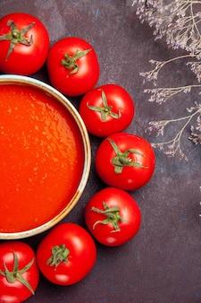 Vista dall'alto deliziosa zuppa di pomodoro circondata da pomodori rossi freschi sullo sfondo scuro salsa di piatti di zuppa di pomodori