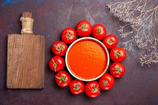 暗い背景に新鮮な赤いトマトで囲まれた上面図おいしいトマトスープトマトスープ皿ソースミール