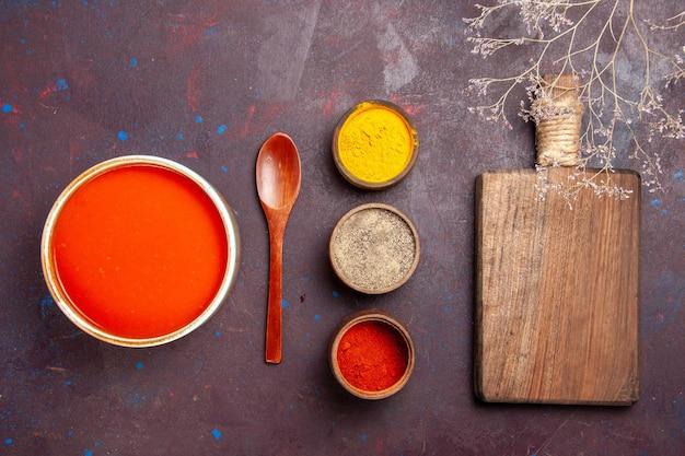 Vista dall'alto deliziosa zuppa di pomodoro cucinata con pomodori freschi con condimenti sullo sfondo scuro piatto di pomodoro zuppa di salsa pasto rosso