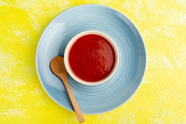 黄色いテーブルの上の青いプレートの中においしいトマトスープ、スープフードミールディナーの上面図