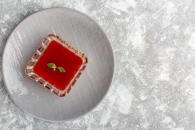 白灰色のテーブルの上の灰色のプレート内のおいしいトマトスープ、スープミールディナー野菜料理の上面図