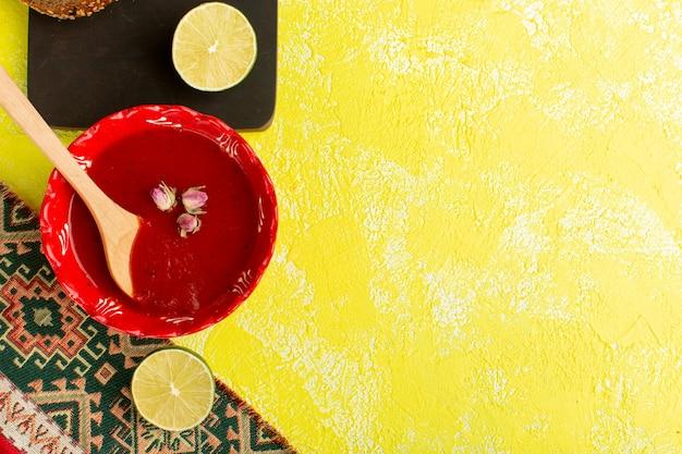 黄色いテーブルにレモンと赤いプレートの中においしいトマトスープ、スープミールディナー野菜料理の上面図