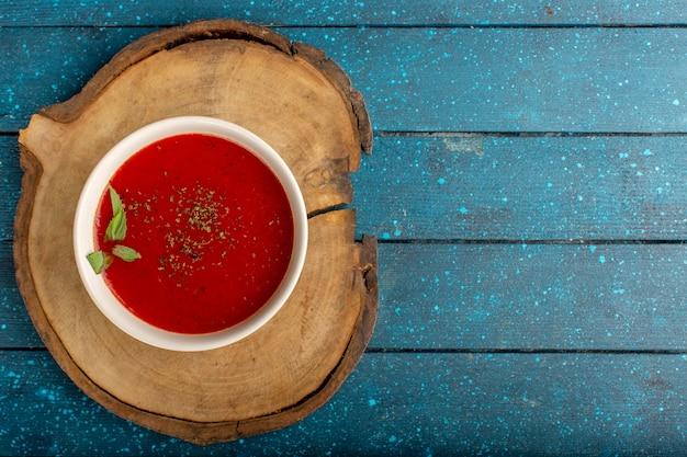 上面図青いテーブルの上のおいしいトマトスープ、スープミールディナー野菜
