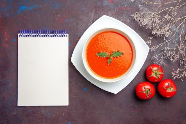 Vista dall'alto deliziosa zuppa di pomodoro piatto gustoso con una foglia all'interno del piatto sullo sfondo scuro