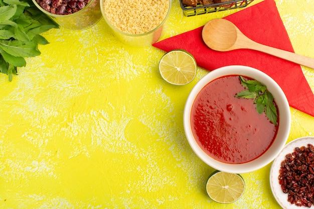 Вид сверху вкусный томатный суп с буханками хлеба с лимоном на желтом столе, суп из овощей на ужин